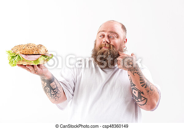Happy fat man showing large burger