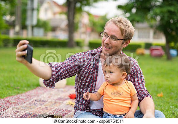 Happy father and baby son taking selfie together outdoors - csp60754511