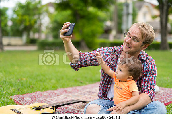 Happy father and baby son taking selfie together outdoors - csp60754513
