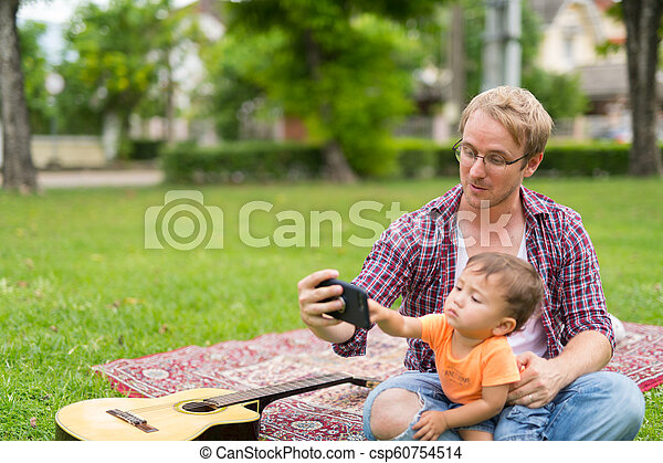 Happy father and baby son taking selfie together outdoors - csp60754514