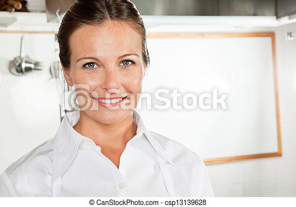 Happy Female Chef In Kitchen - csp13139628