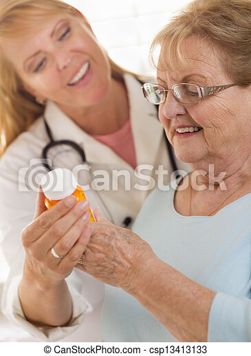 Happy Female Doctor or Nurse Explaining Prescription to Senior Adult Woman. - csp13413133