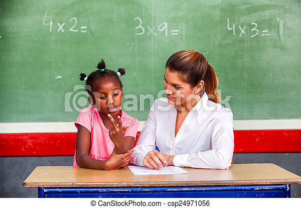 Happy Female Teacher And Afro American Schoolgirl Discussing Math Questions In Front Of Chalkboard