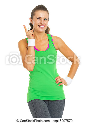 Happy fitness young woman pointing on copy space - csp15997570