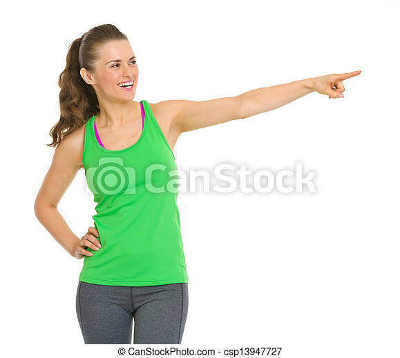 Happy fitness young woman pointing on copy space - csp13947727
