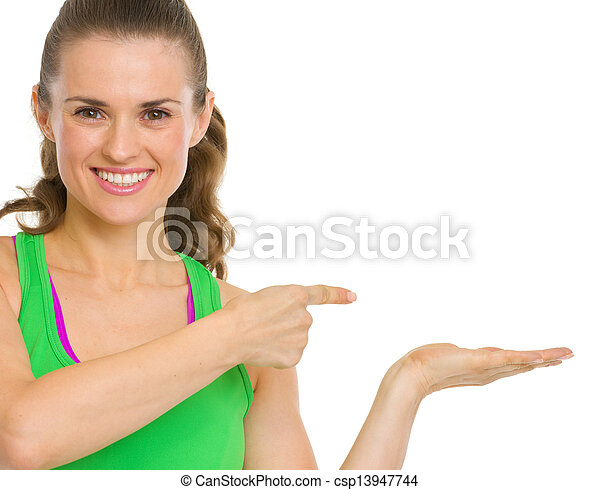 Happy fitness young woman presenting something on empty palm - csp13947744