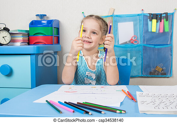 Happy five year old girl chooses the correct pencil drawing at the table - csp34538140