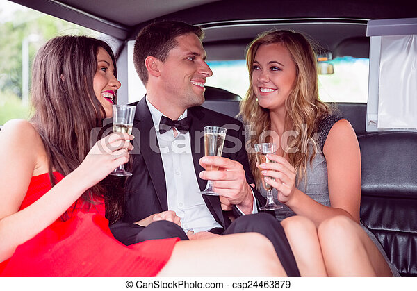 Happy friends drinking champagne in limousine - csp24463879