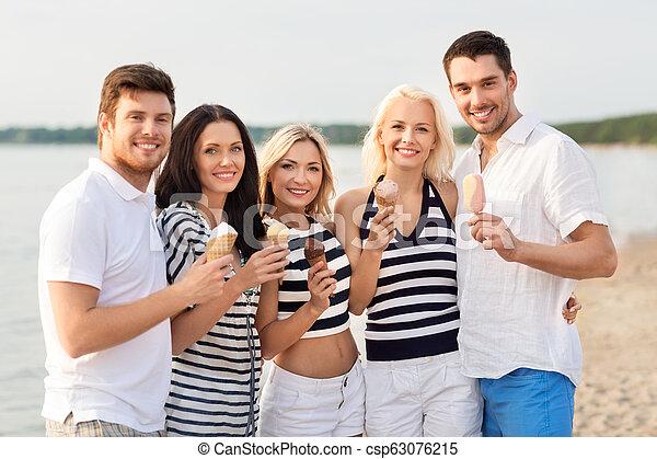 happy friends eating ice cream on beach - csp63076215