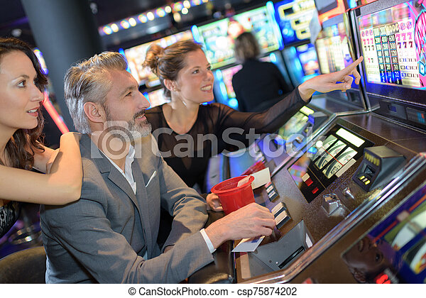 happy friends having fun together with slot machine - csp75874202