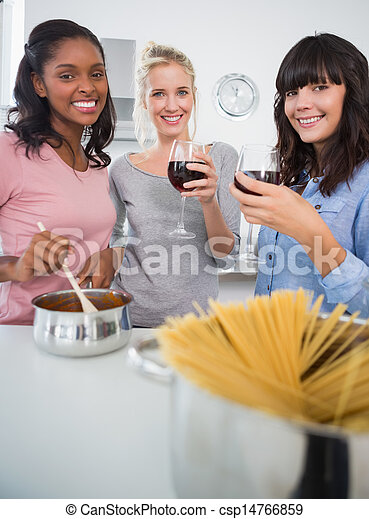Happy friends making spaghetti dinner together and drinking red wine smiling at camera in kitchen - csp14766859