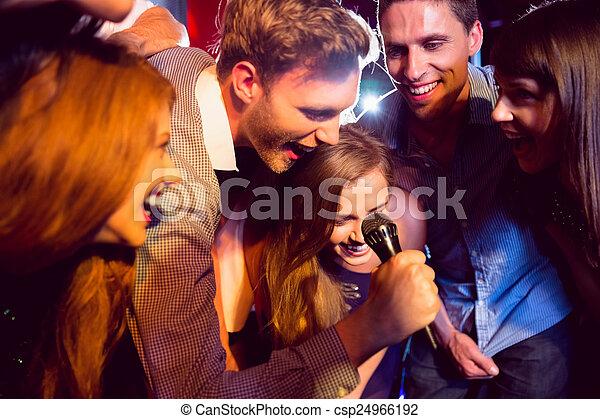 Happy friends singing karaoke together - csp24966192