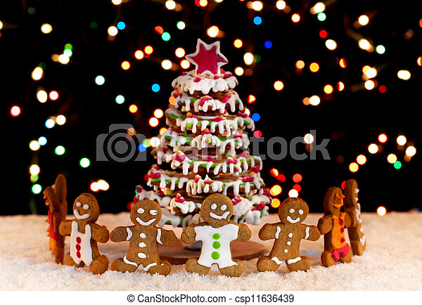 Happy gingerbread people around the christmas tree - csp11636439