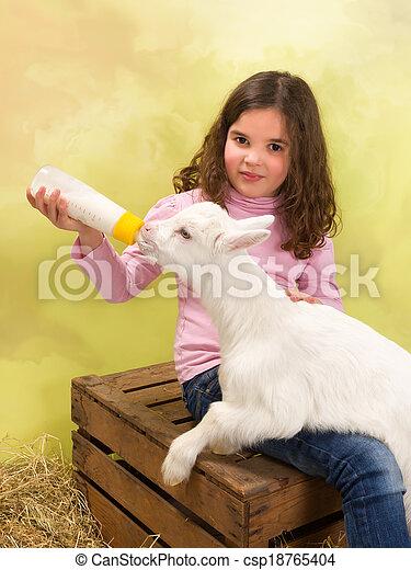Happy girl feeding baby goat - csp18765404