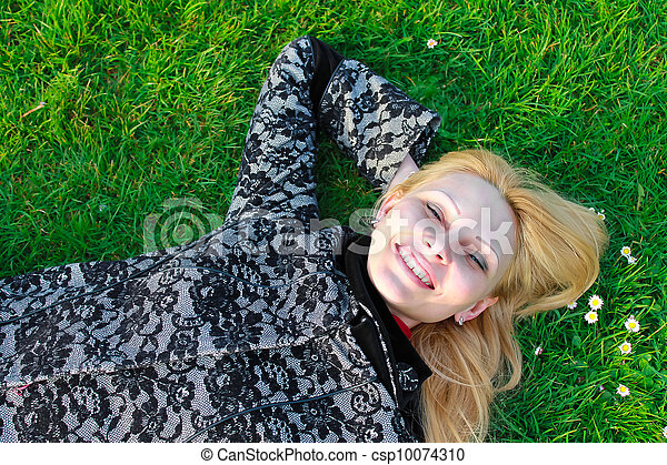 Happy girl lies on a blooming meadow in the early spring morning - csp10074310
