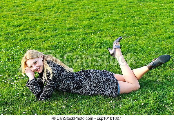Happy girl lies on a blooming meadow in the early spring morning - csp10181827