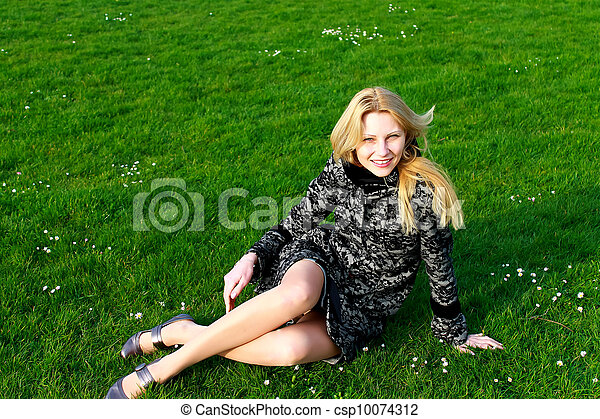 Happy girl sits on a blooming spring meadow in the early morning - csp10074312