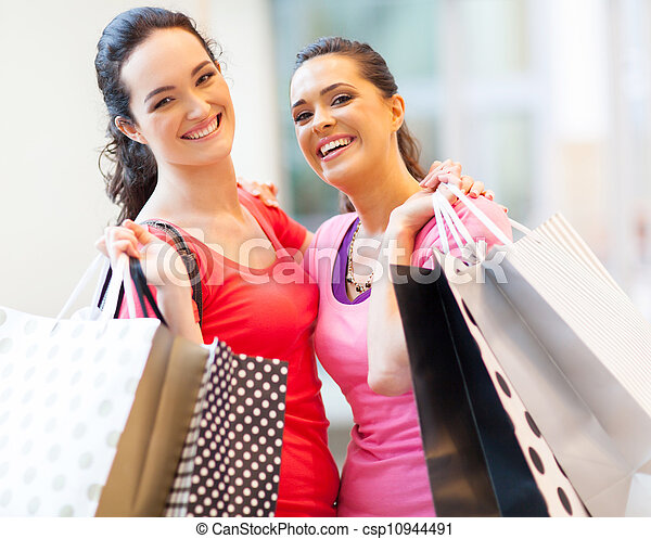 happy girls with shopping bags in mall - csp10944491
