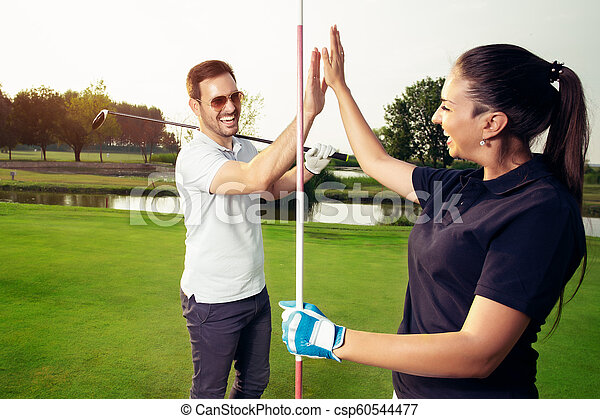 Happy golf player couple giving high five while standing on field - csp60544477