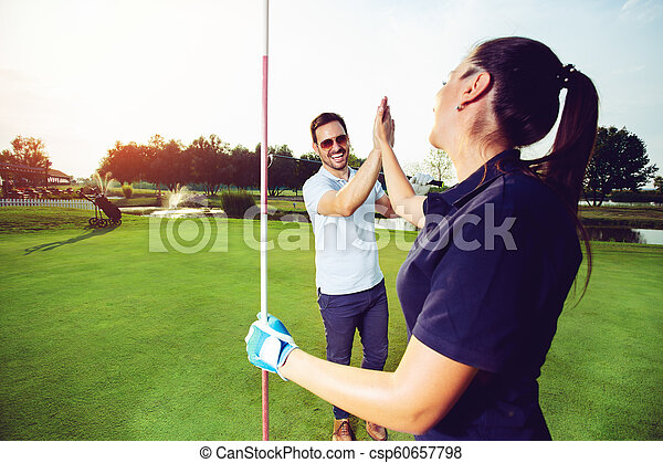 Happy golf player couple giving high five while standing on field - csp60657798