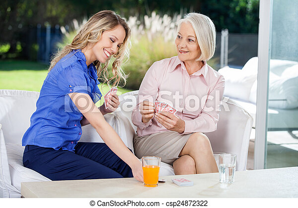 Happy Grandmother And Granddaughter Playing Cards - csp24872322