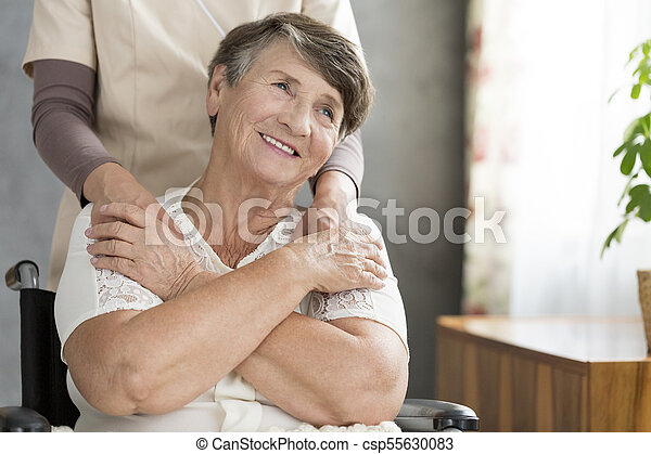Happy grandmother supported by nurse - csp55630083