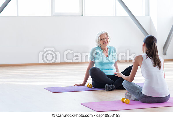 Happy grey haired woman looking at her fitness coach - csp40953193