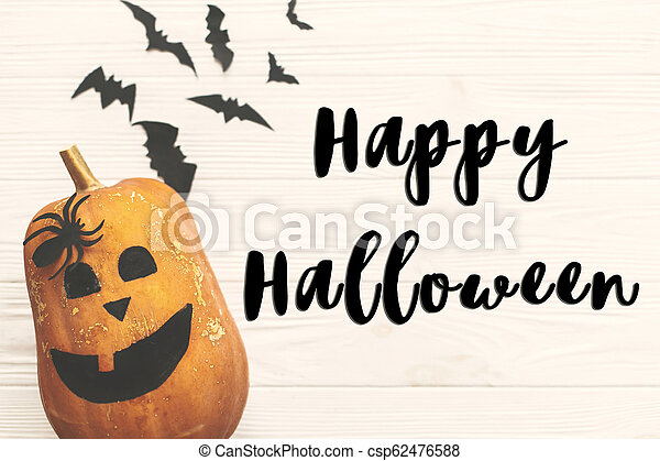 Happy Halloween text sign, flat lay. Halloween pumpkin Jack o Lantern with bats, spiders top view on white rustic wooden background. Season's greeting card - csp62476588