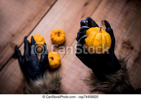 Happy Halloween. Werewolf or zombie hands holding pumpkin for trick or treat party. - csp74456820