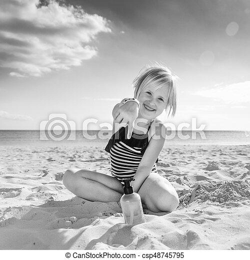 cbeeabc9eb Happy healthy child in swimwear on beach pointing at sun screen. Sun ...