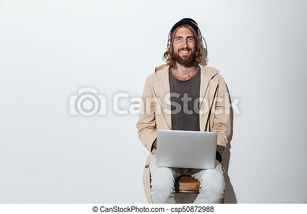 Happy hipster man looking camera using laptop computer. - csp50872988