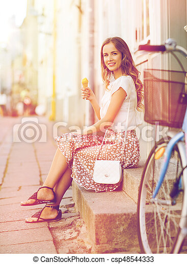 happy hipster woman with bike eating ice cream - csp48544333