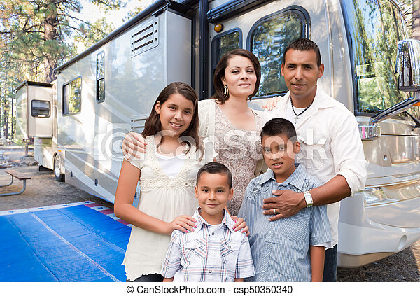 Happy Hispanic Family In Front of Their Beautiful RV At The Campground. - csp50350340