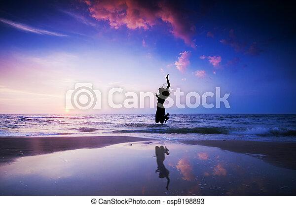 Happy jump jumping on beach - csp9198893