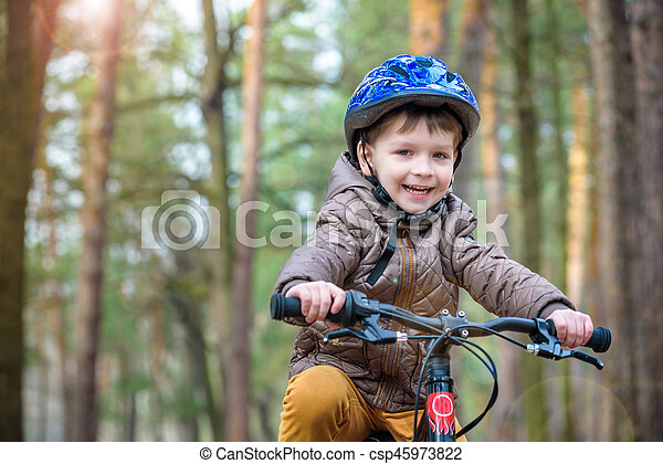 Happy kid boy of 3 or 5 years having fun in autumn forest with a bicycle on fall day. Active child wearing bike helmet. Safety, sports, leisure with kids concept. - csp45973822