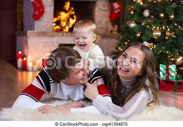 Happy kid boy playing with his parents under the christmas tree - csp41394870