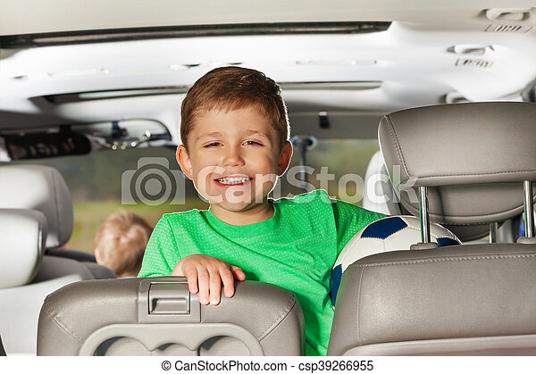 Happy Kid Boy Sitting In The Car And Holding Ball