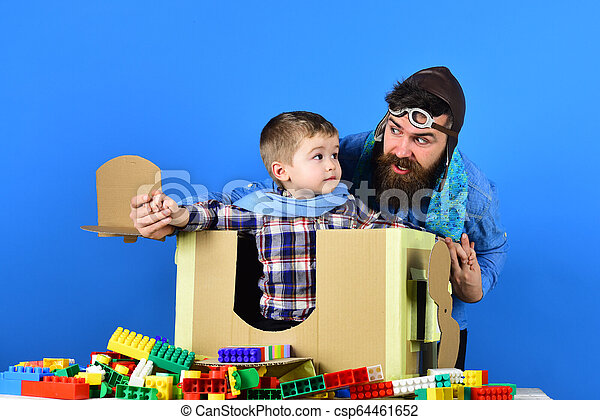 Happy kid playing with toy airplane on blue background. Developing funny games with toddler. Boy wearing blue scarf sits in small cardboard plane. Family leisure at home. Father and son together - csp64461652