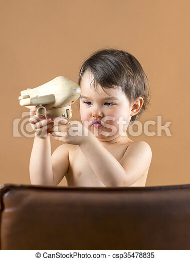 Happy kid playing with toy airplane. Studio shot. - csp35478835