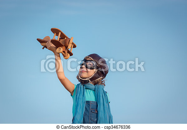 Happy kid playing with wooden toy airplane - csp34676336