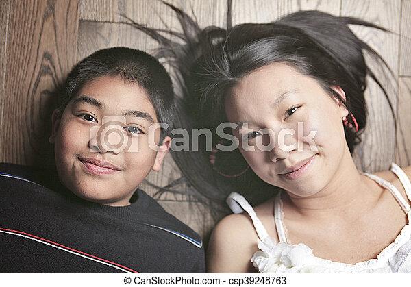 happy kids on the floor laying on wooden floor - csp39248763