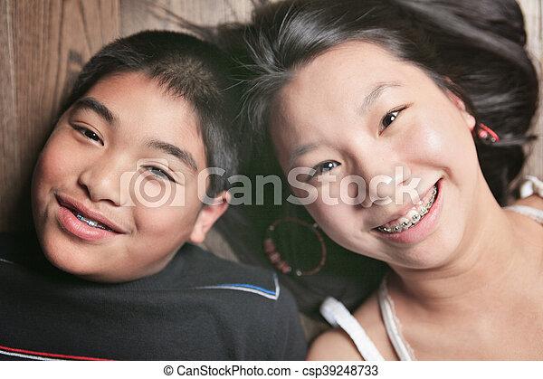 happy kids on the floor laying on wooden floor - csp39248733
