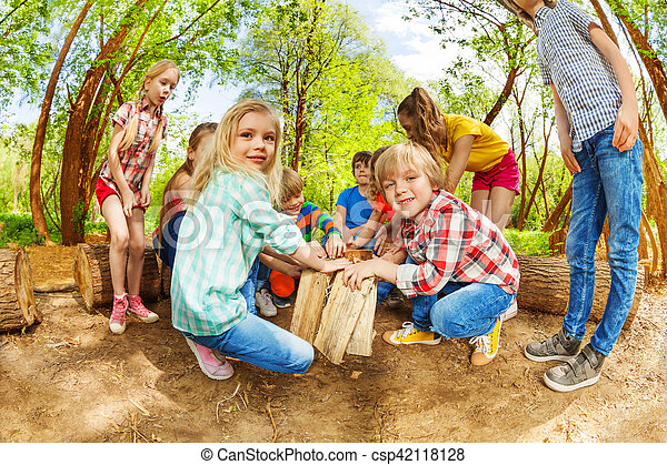 Happy kids playing with wooden logs in the forest - csp42118128