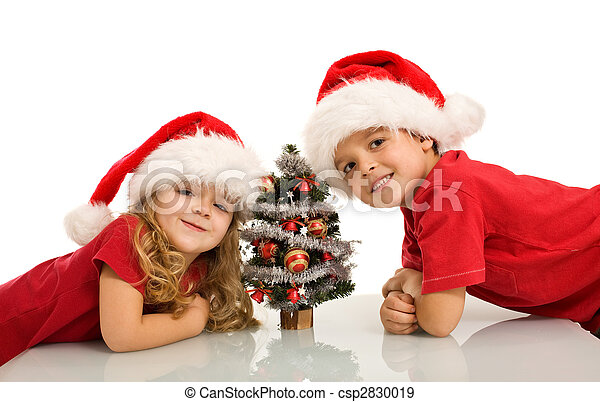 Christmas Hats For Kids.Happy Kids With Santa Hats And Small Christmas Tree