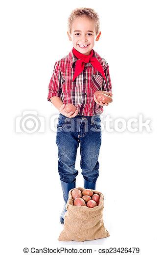 Happy little agriculturist boy showing potato harvest - csp23426479