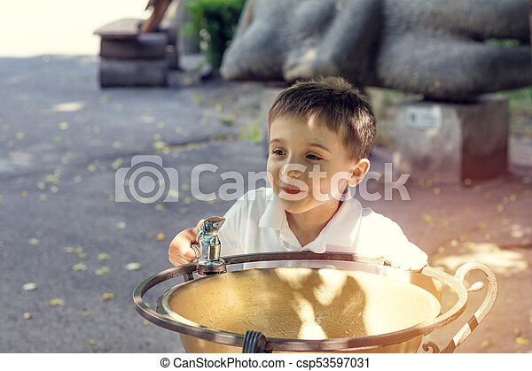 Happy little boy drinking water from fountain in the city park on a summer sunny day. Close up. Beautiful summer background with copy space - csp53597031