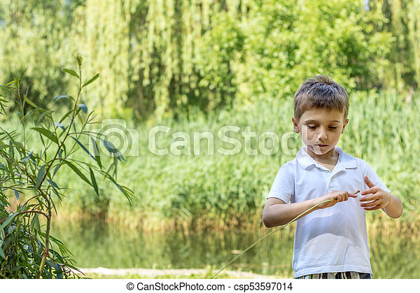 Happy little boy playing at the pond in the city park on a summer sunny day. Close up. Beautiful summer background with copy space - csp53597014