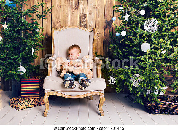 Happy little boy playing near the Christmas tree - csp41701445