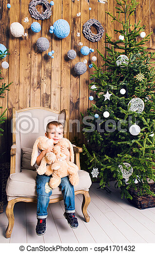 Happy little boy playing near the Christmas tree - csp41701432