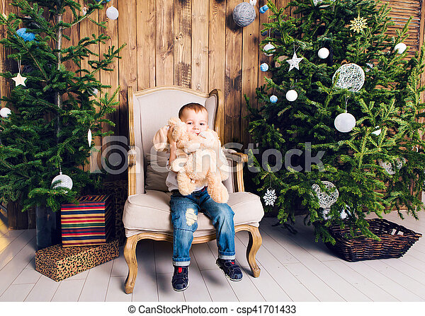 Happy little boy playing near the Christmas tree - csp41701433